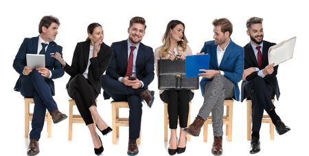 Photo for Team of 6 businessmen talking while one is gossiping and pointing, holding newspaper, tablet, clipboard and briefcase while sitting on chairs on white studio background - Royalty Free Image