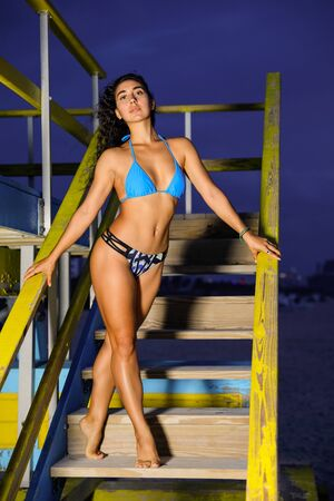 Photo pour Sey young bikini model posing on a lifeguard hut in Miami Beach shot with flash at dawn - image libre de droit