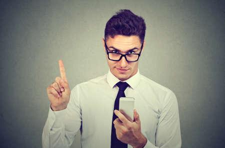 Photo pour Business man with smartphone showing no, attention with finger hand gesture. Blocking dangerous adult contents. Parental control concept - image libre de droit