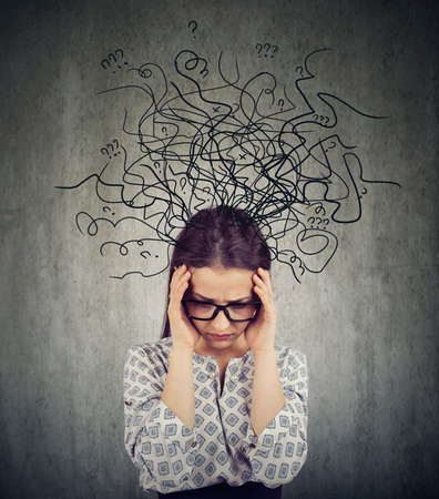 Foto de Girl in glasses having problems with mental health and looking deep in chaos on gray background - Imagen libre de derechos