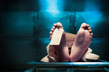 Photo for Grungy photo of feet with toe tag on a morgue table - Royalty Free Image