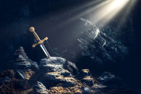 Photo for High contrast image of Excalibur, sword in the stone with light rays and dust specs in a dark cave - Royalty Free Image