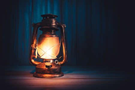 Foto de Kerosene lamp or lantern on a wooden background with dramatic lighting - Imagen libre de derechos