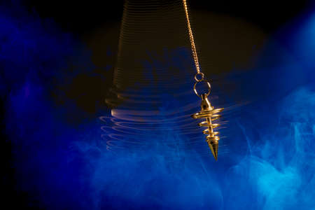 Foto de Pendulum used for hypnotism and readings swinging with motion blur - Imagen libre de derechos