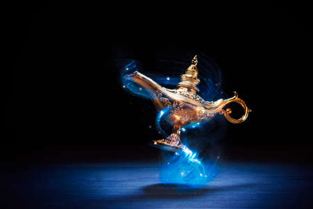 Foto de Magic genie lamp floating on a dark background - Imagen libre de derechos
