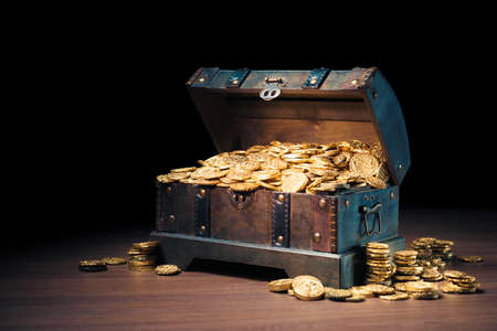 Photo for Open treasure chest filled with gold coins / HIgh contrast image - Royalty Free Image
