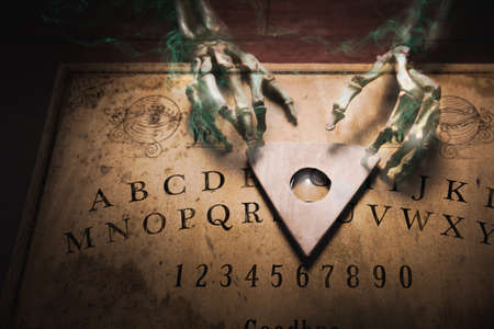 Photo for Talking board with a ghost touching the planchette, high contrast image - Royalty Free Image