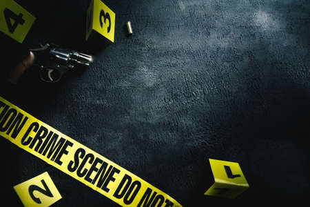 Photo pour Crime scene concept with a gun and evidence markers , high contrast image - image libre de droit