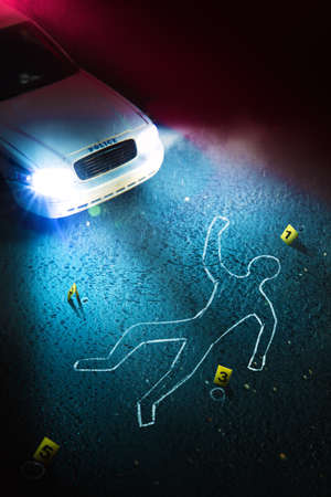 Foto de Crime scene with body outline, evidence markers and a police car with dramatic lighting - Imagen libre de derechos