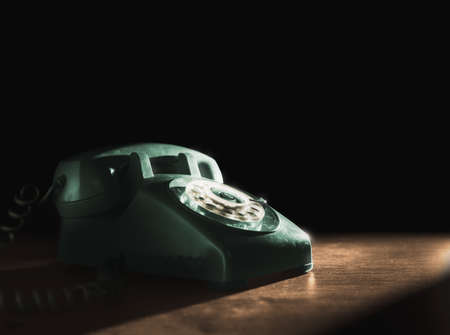 Photo for High contrast image of a vintage telephone with rotary dial on a wooden background - Royalty Free Image