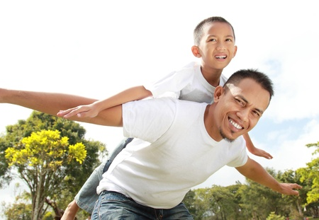 Man smiling giving young boy piggyback ride