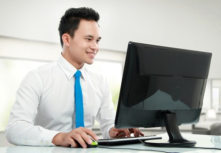 Portrait of a young business man with computer working in the office