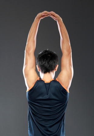 young fitness man making stretching exercises seen from behind