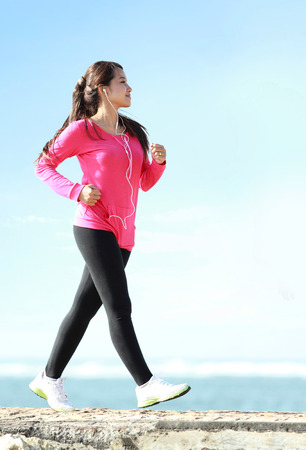 Foto per Happy healthy girl doing a brisk walking on the beach - Immagine Royalty Free