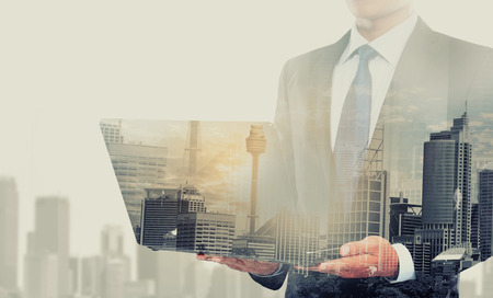 Foto de Double exposure of city and businessman using laptop computer - Imagen libre de derechos