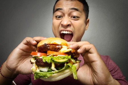 Foto per A portrait of young man have a great desire to eat a burger - Immagine Royalty Free