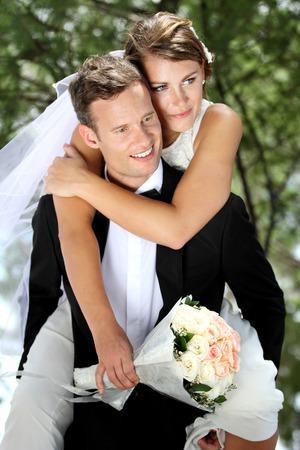 Foto de portrait of gentleman groom pickaback his beautiful bride - Imagen libre de derechos