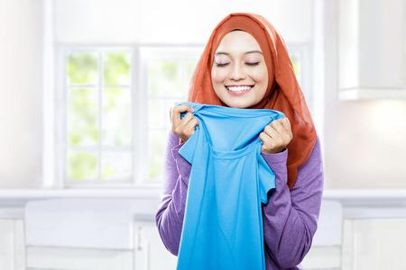 Foto de portrait of young woman wearing hijab holding and smelling the fresh clean laundry - Imagen libre de derechos