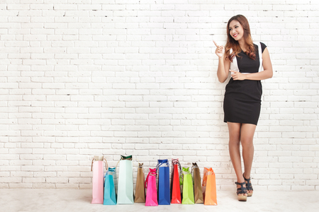 Photo pour full body portrait of beautiful young woman standing next to shopping bags while pointing at copy space on white brick wall background - image libre de droit