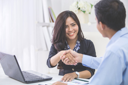 Photo for Pretty asian business woman shaking hands with businessman in her office during meeting - Royalty Free Image