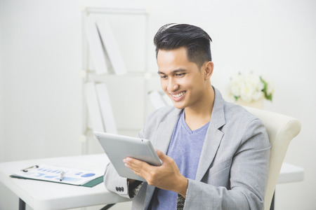 Foto de portrait of handsome asian businessman using tablet pc at his office - Imagen libre de derechos