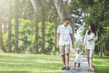 Photo pour portrait of father, mother and their  baby walk along the park together - image libre de droit