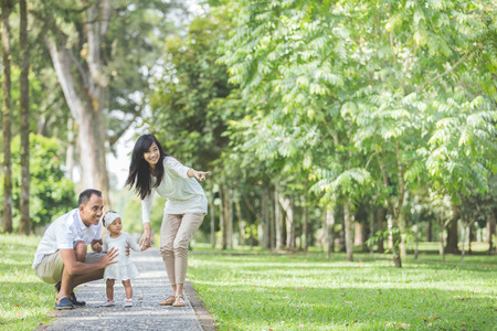 Photo pour portrait of Beautiful family with cute baby in the park having fun together - image libre de droit