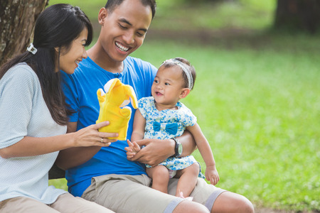 portrait of Happy family sitting on a bench in the park and playing with hand doll