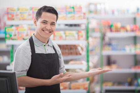 Foto de Portrait of a smiling shopkeeper in a grocery store welcoming customer - Imagen libre de derechos
