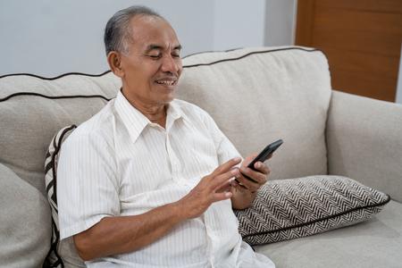 Photo pour old man using smartphone at home - image libre de droit