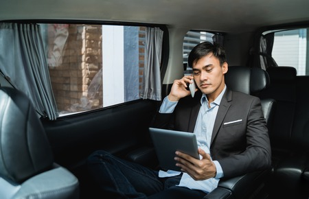 Photo pour businessman calling by phone and using tablet  in the car - image libre de droit