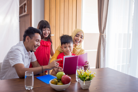 Foto de asian family reading a book together at home - Imagen libre de derechos