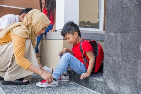 Foto de help her son to put on his shoes - Imagen libre de derechos