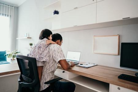 Foto de parent interrupts by her daughter while working in the office - Imagen libre de derechos
