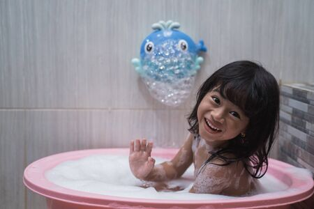 Photo pour Asian little girl smilling when take a bath with foam - image libre de droit
