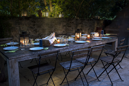 Photo for large rustic table on the terrace prepared for a outside dinner with friends from the evening until late at night - Royalty Free Image