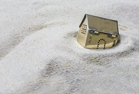 Photo pour built on sand, small golden model house sinking into the sand, concept of risk in real estate financing, or investing in gold, selected focus, Copy Space - image libre de droit