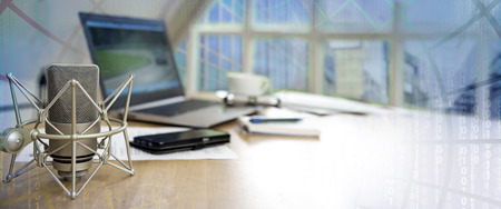 Foto de business workspace for international  journalism with microphone, laptop, cell phone and notepad on a desktop, panoramic banner with blurred matrix in the background, copy space - Imagen libre de derechos