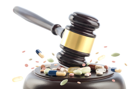 Foto de Judge gavel beats on tablets and pills,  judge cocept, crime with drugs, medicine or doping, isolated on a white background, selected focus, motion blur - Imagen libre de derechos