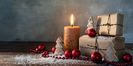 Photo for two gift boxes and a burning candle decorated with red christmas baubles and small wooden toy trees in some snow on rustic wood, vintage background with large copy space, panorama format, selected focus, narrow depth of field - Royalty Free Image