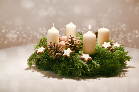 Foto de First Advent - decorated Advent wreath from fir and evergreen branches with white burning candles - Imagen libre de derechos