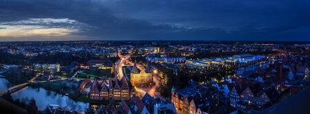 Foto de Luebeck, Germany – December 17, 2019:  Aerial night view panorama of the illuminated city of Luebeck in winter with Holstentor, historic Salzspeicher houses and the river Trave, long term exposure at blue hour, copy space - Imagen libre de derechos