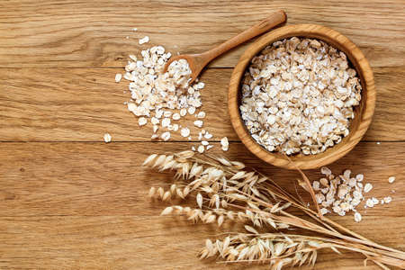 Foto de Rolled oats and oat ears of grain on a wooden table, copy space - Imagen libre de derechos