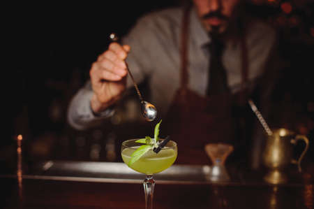 Photo for Close-up of bartender making green cocktail in bar - Royalty Free Image