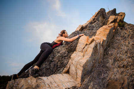 Female extreme climber conquers the steep rocks