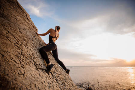 Female rock climber watching sunset over the sea