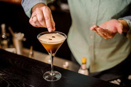 Photo pour classy bartender garnish martini espresso cocktail drink white foam coffee bean on top bar counter - image libre de droit