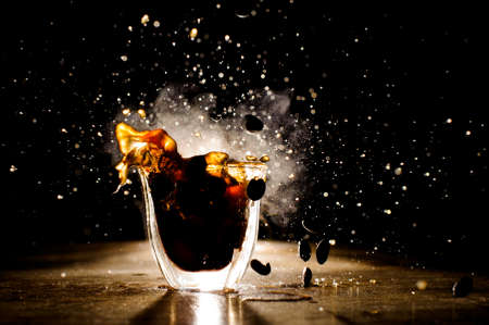 Foto de Splashes of coffee from hot mug located on the wooden table on the dark background - Imagen libre de derechos