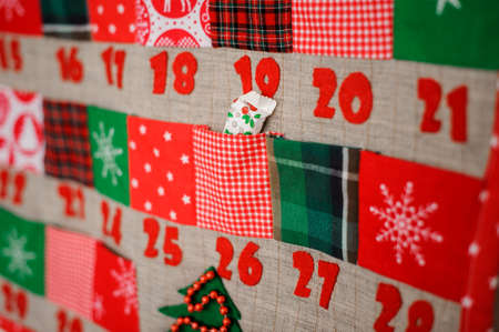 Photo for Soft and textile Christmas calendar with pockets decorated with textile christmas patterns and trees hanging on the white wall - Royalty Free Image
