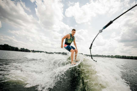 Photo pour Young brunette caucasian man riding stylish wake board on high wave of motorboat, spiting out spray - image libre de droit